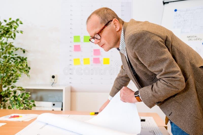 Leverantör som analyserar plan på ritning på arbetsplatsen royaltyfri foto