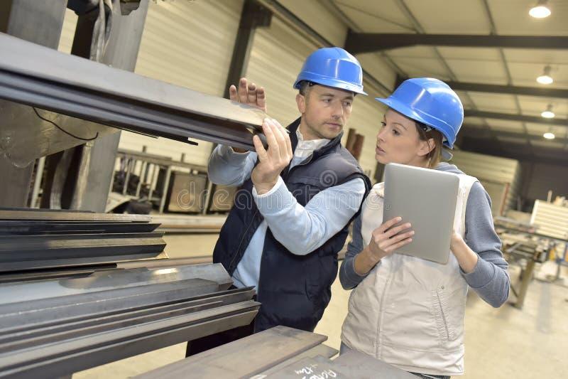 Leverantör som diskuterar med teknikern på produktionen royaltyfri bild