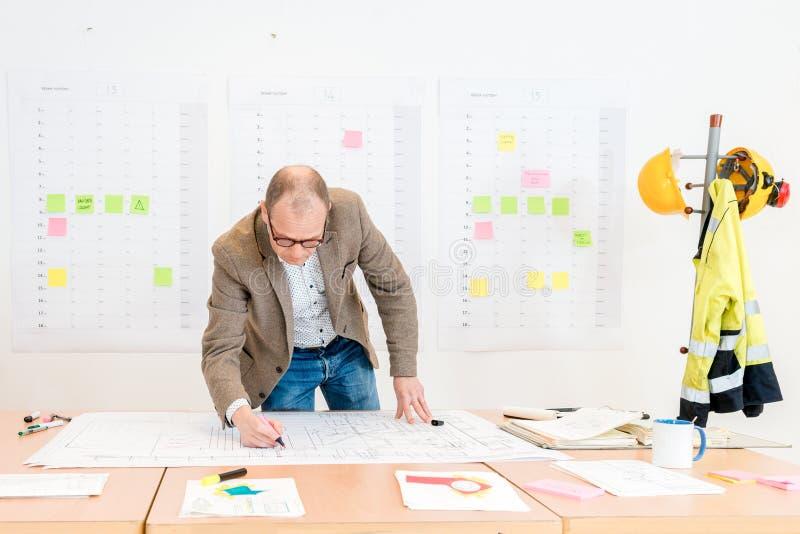 Leverantör som gör arkitektoniskt plan i konferensrum arkivbilder