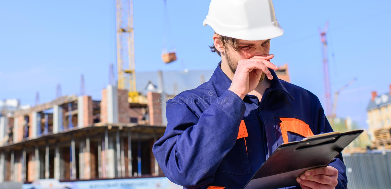 Leverantörkontroll enligt plan Iscensätta den skyddande hjälmställningen framme av bakgrund för blå himmel Byggmästaretekniker fotografering för bildbyråer