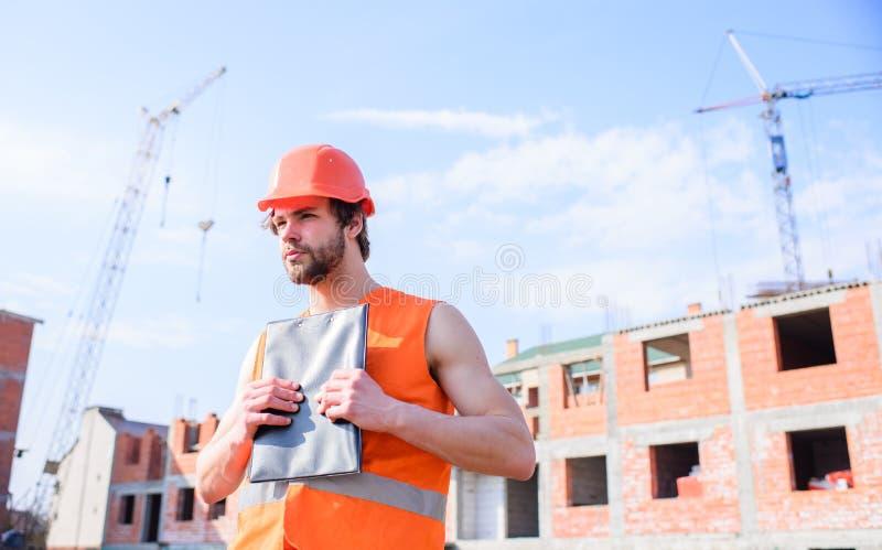 Leverantörkontroll enligt plan Skyddande hjälmställning för grabb framme av byggnad som göras ut ur röda tegelstenar kontroll arkivfoto