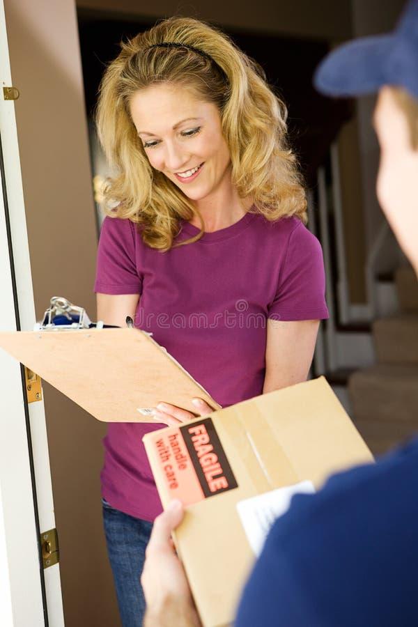 Levering: Huisvrouw Signs voor Pakket royalty-vrije stock afbeelding