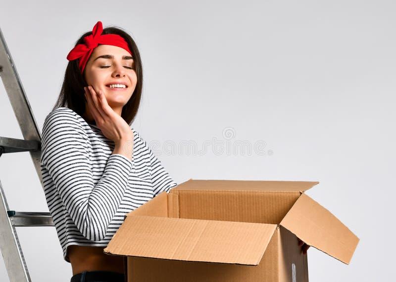 Levering, verhuizing en het uitpakken Glimlachend jonge die het kartondoos van de vrouwenholding op witte achtergrond wordt ge?so stock foto's