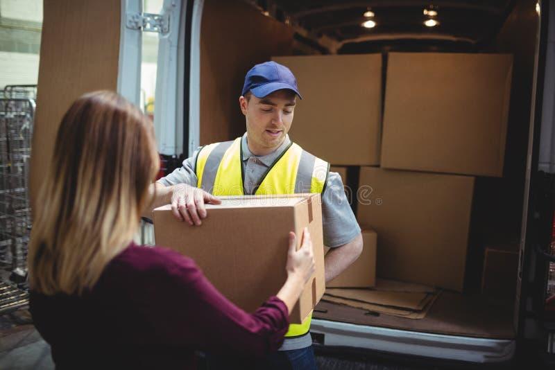 Leveringsbestuurder die pakket overhandigen aan klant buiten bestelwagen royalty-vrije stock foto
