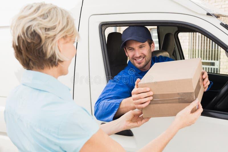 Leveringsbestuurder die pakket overhandigen aan klant in zijn bestelwagen stock afbeelding