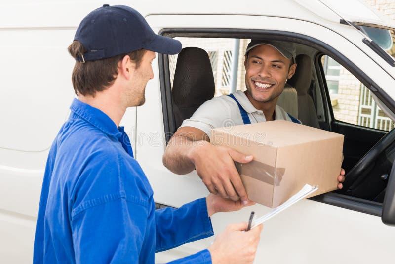 Leveringsbestuurder die pakket overhandigen aan klant in zijn bestelwagen stock foto