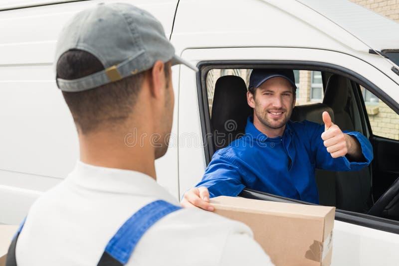 Leveringsbestuurder die pakket overhandigen aan klant in zijn bestelwagen stock afbeeldingen
