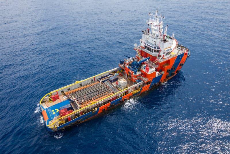 Leveringsboot die hulpmiddel voor zeebooreiland aan compleationolie en gasput komen te ontladen stock afbeeldingen