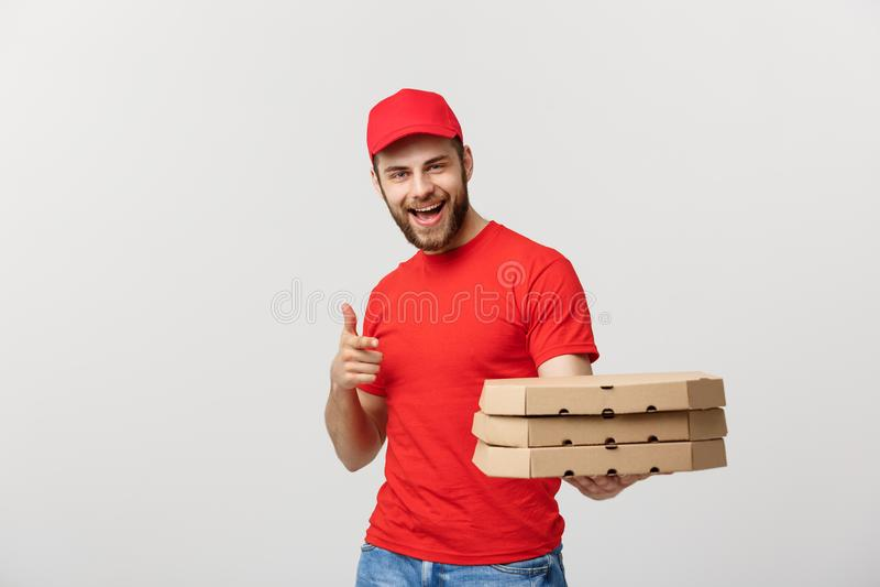 Leveringsconcept: De knappe Kaukasische mens die van de Pizzalevering vinger richten Geïsoleerdg over grijze achtergrond royalty-vrije stock afbeelding