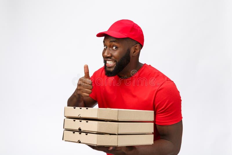 Leveringsconcept - het Portret van de Gelukkige Afrikaanse Amerikaanse een pakket van de pizzadoos houden en leveringsmens die be stock fotografie