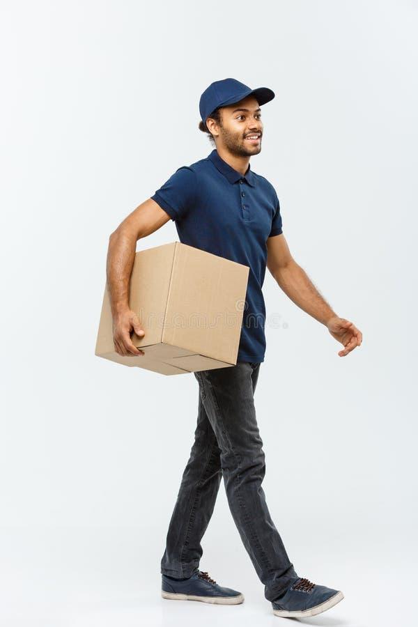 Leveringsconcept - Portret van de Gelukkige Afrikaanse Amerikaanse leveringsmens die in blauwe doek lopen te verzenden een doospa royalty-vrije stock foto's