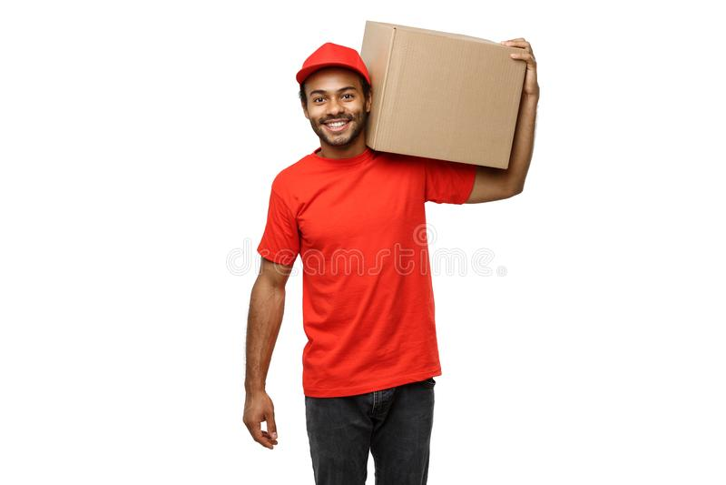 Leveringsconcept - Portret van de Gelukkige Afrikaanse Amerikaanse leveringsmens die in rode doek een doospakket houden Geïsoleer stock foto's