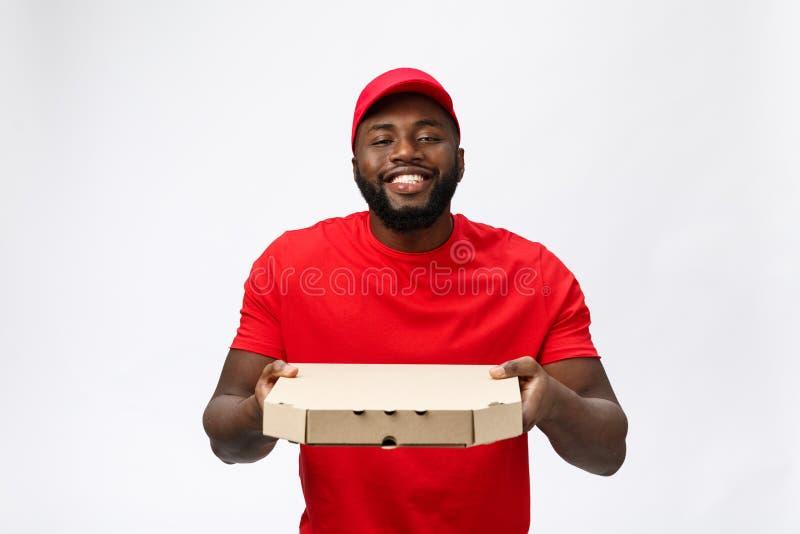 Leveringsconcept - Portret van de Knappe Afrikaanse Amerikaanse mens van de Pizzalevering Geïsoleerd op grijze studioachtergrond  stock fotografie