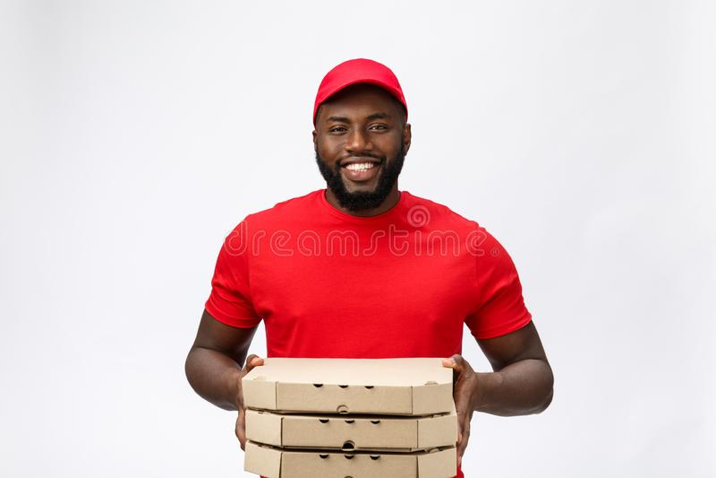 Leveringsconcept - Portret van de Knappe Afrikaanse Amerikaanse mens van de Pizzalevering Geïsoleerd op grijze studioachtergrond  stock foto