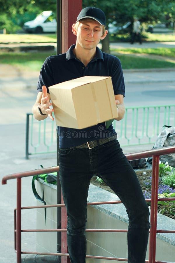 Leveringsmens die Pakketdoos leveren aan Huiseigenaar stock foto