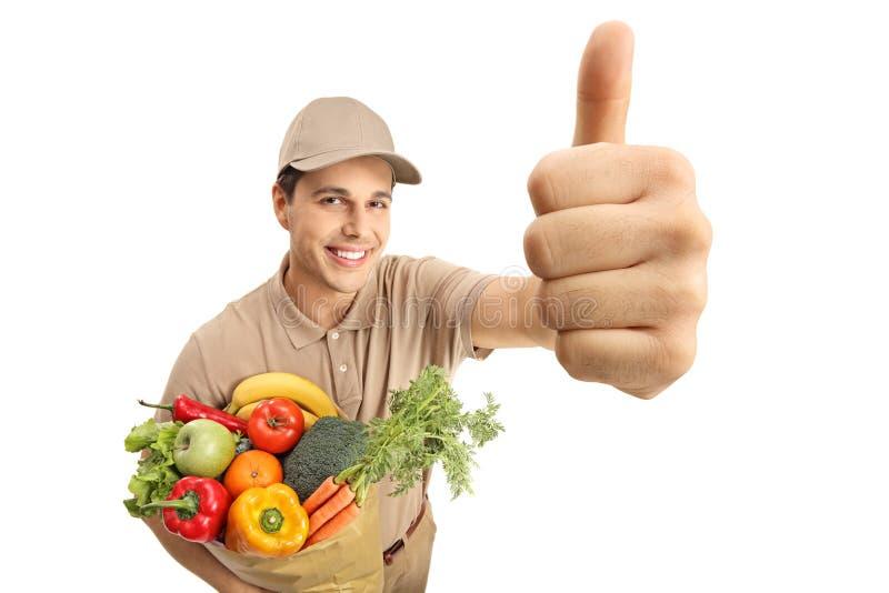 Leveringsmens met een zak van kruidenierswinkels die een duim op gebaar maken stock foto