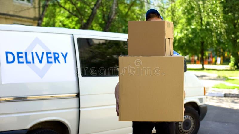 Leveringswerkman die vele kartondozen, de uitdrukkelijke dienst van de pakketverzending houden royalty-vrije stock foto