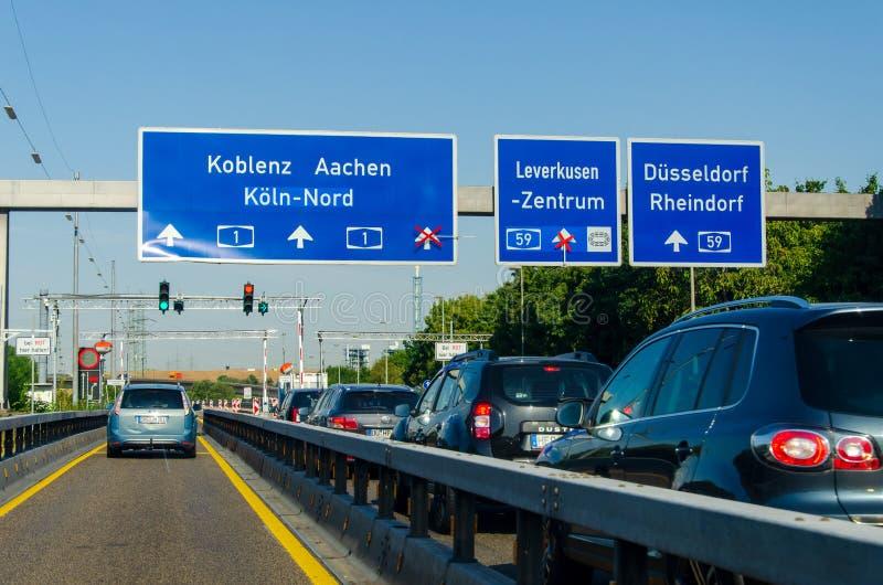Leverkusen, Tyskland - 26 juli 2019: Vägtrafik på tyska motorvägen A1 med vägmärken och trafikljus Bilkörning royaltyfria foton