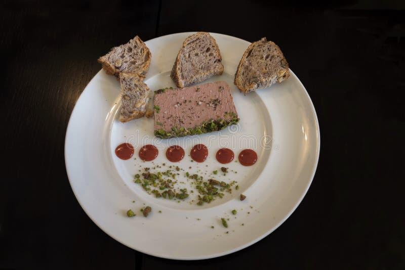 LeverPate med pistascher, svart bröd med valnötter och röda droppar av driftstopp royaltyfria foton