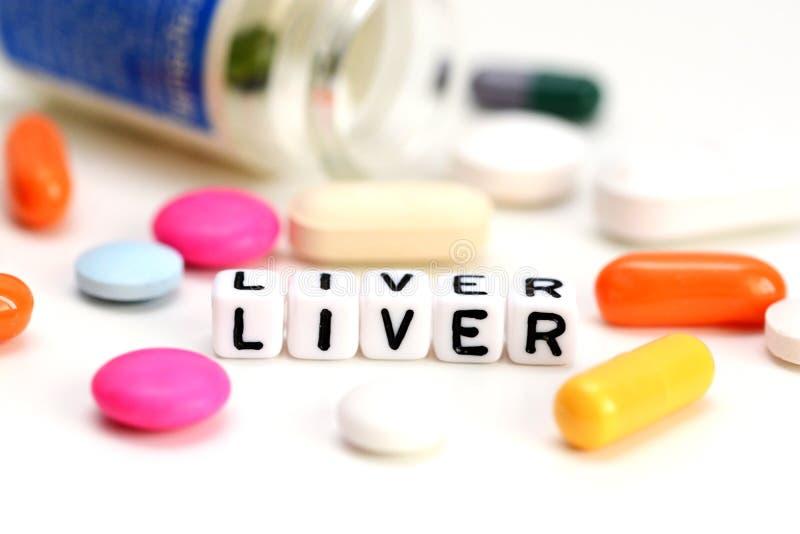 Leverproblembegrepp med närbild av färgrika preventivpillerar och leverordet på vit bakgrund royaltyfri bild