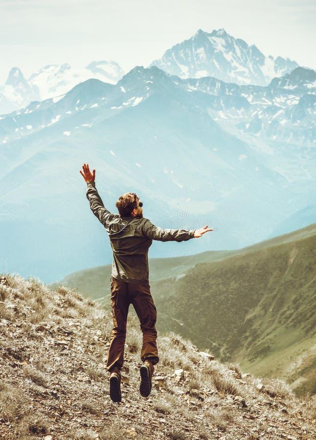 Levitación de salto del hombre feliz a los picos de montañas fotos de archivo