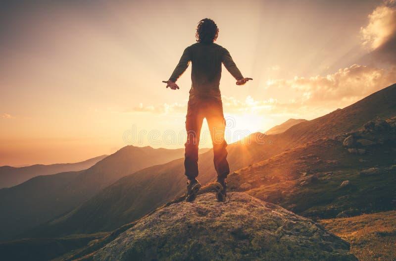 Levitación del vuelo del hombre joven que salta en montañas de la puesta del sol fotos de archivo