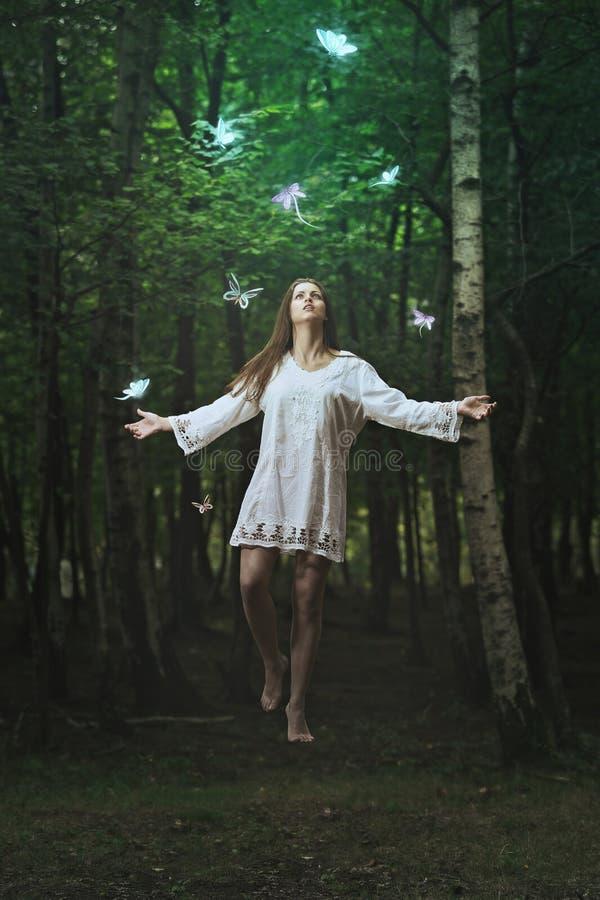 Levitación hermosa de la mujer en un bosque oscuro fotografía de archivo