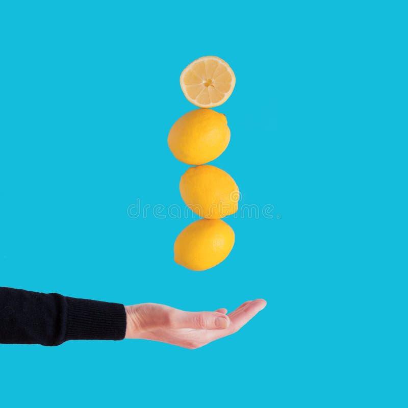 Levitando limões com mão das mulheres no fundo azul Copie o espaço foto de stock