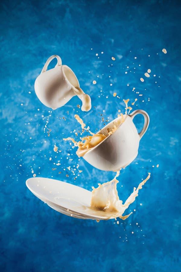 Levitando o copo, os pires e a desnatadeira com espirro do leite e do café planta-baseados no azul imagem de stock