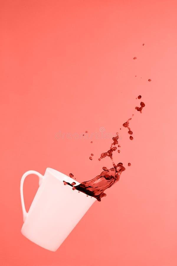 Levitar a caneca de café com espirra Conceito do café Tendência mínima da arte Fundo cor-de-rosa contínuo Tema coral de vida - co fotografia de stock royalty free