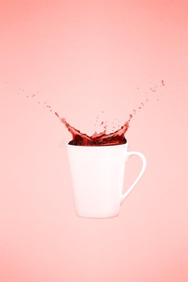 Levitar a caneca de café com espirra Conceito do café Tendência mínima da arte Fundo cor-de-rosa contínuo Tema coral de vida - co foto de stock royalty free