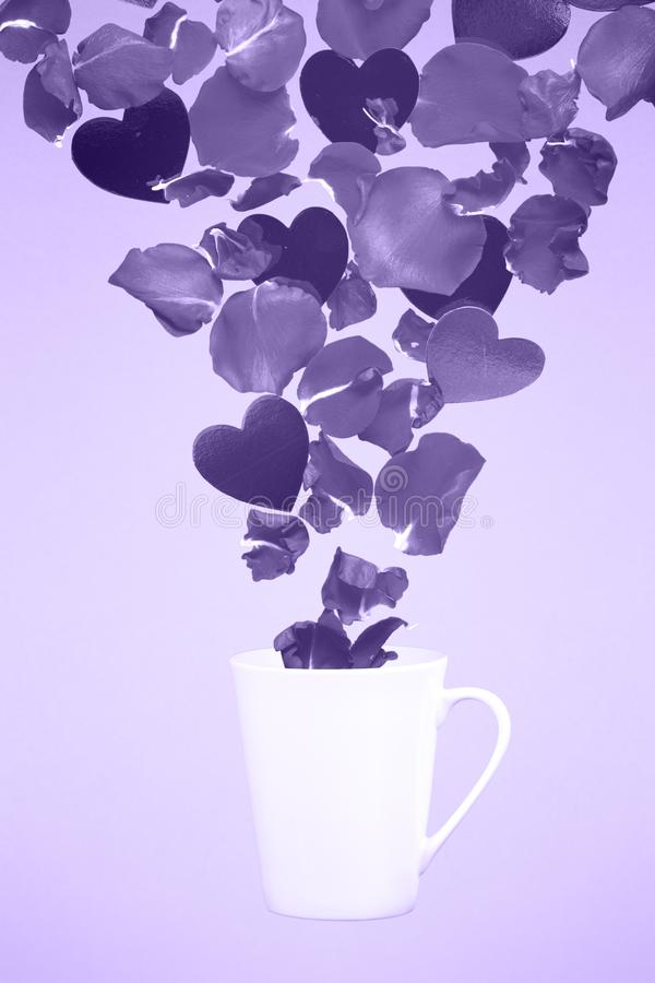 Levitar a caneca de café com espirra das pétalas cor-de-rosa e dos corações S fotos de stock