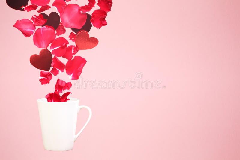 Levitar a caneca de café com espirra das pétalas cor-de-rosa e dos corações Surpresa, feriado e conceito do amor do café Tendênci imagens de stock royalty free