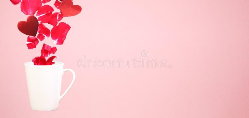 Levitare la tazza da caffè con spruzza dei petali rosa e dei cuori Sorpresa, festa e concetto di amore del caffè Tendenza minima  immagini stock