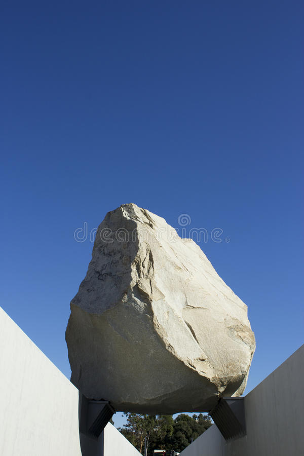 Levitated Mass Over Walkway While Visitors Engage by Walking Under. The Levitated Mass sits over a sunken walkway at the Los Angeles County Museum of Art. The royalty free stock photo