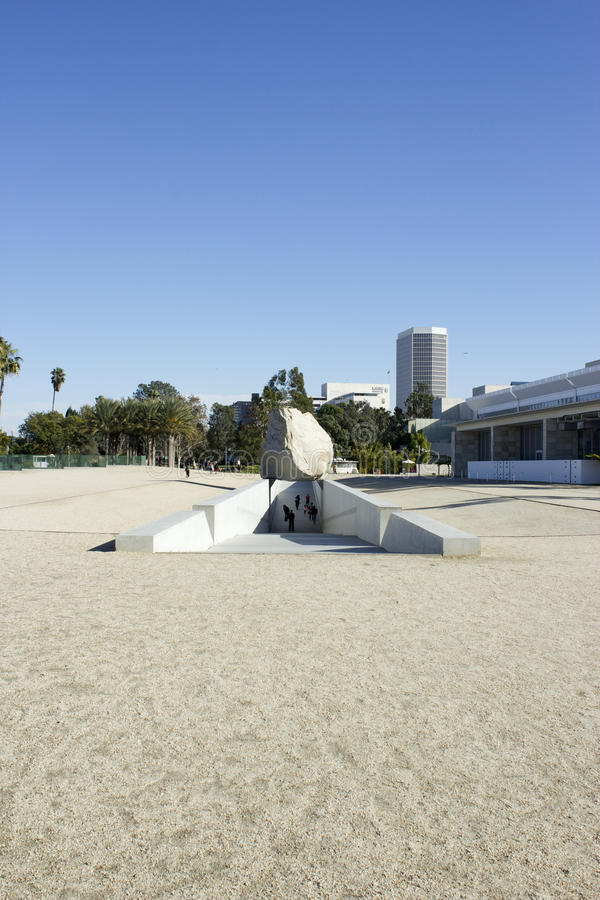 Levitated Mass Over Walkway While Visitors Engage by Walking Under. The Levitated Mass sits over a sunken walkway at the Los Angeles County Museum of Art. The stock photography