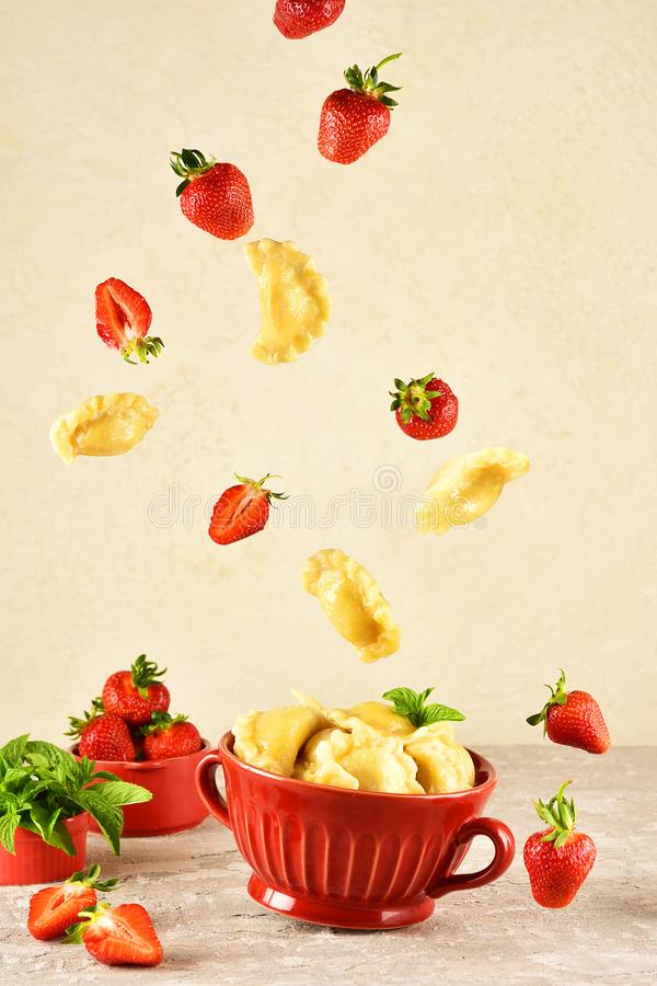 Levitating food. Pierogi. Dumplings with with strawberry are flying. Ready meal. Levitating food. Pierogi. Dumplings with with strawberry are flying. Ready meal royalty free stock photo