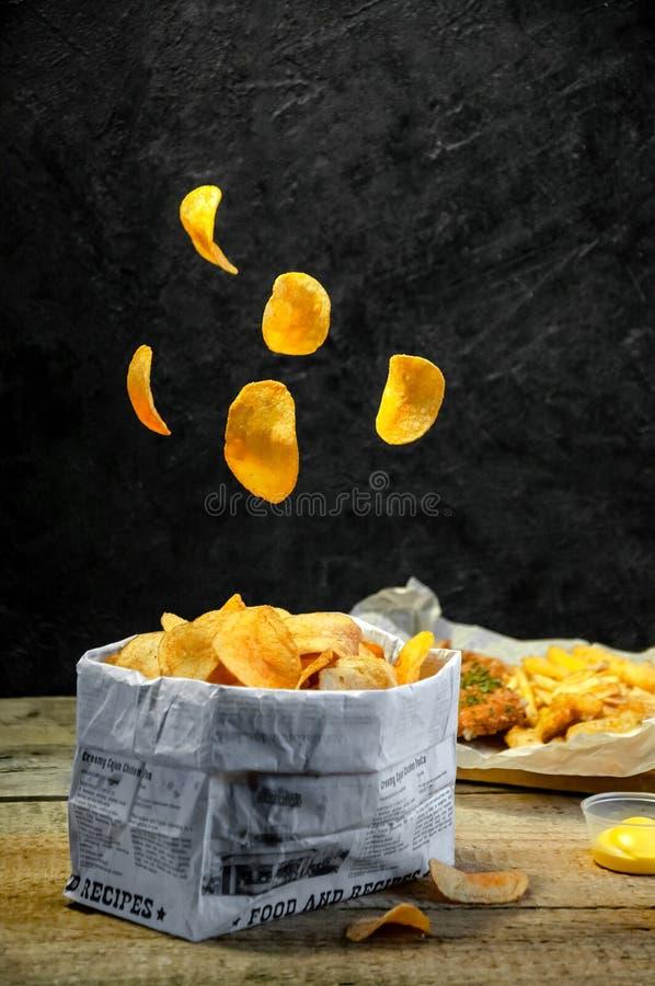 levitation Fast food Petiscos salgados Microplaquetas de batata, batatas fritas, anéis de cebola, varas do queijo, pepitas Alimen imagem de stock royalty free