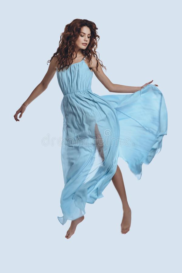 Levitation. Full length studio shot of attractive young woman in elegant dress hovering against grey background royalty free stock images