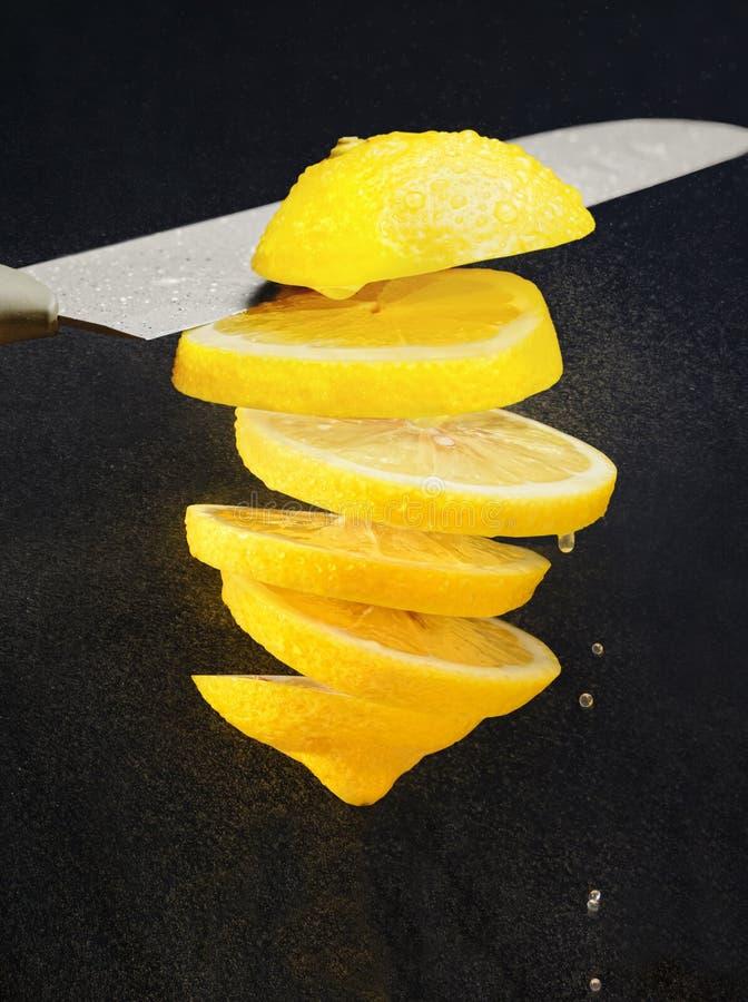levitation Slica do limão cortado com um knive pulverizadores do suco foto de stock royalty free