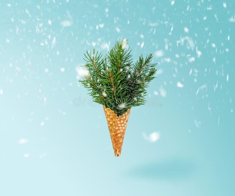 Levitazione del cono gelato dell'albero di Natale in neve sul fondo blu di Ligth Concetto di nuovo anno Composizione minima in fe fotografie stock