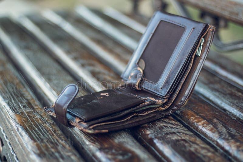 Lewica bardzo stary kieszeni gotówki portfel na drewnianej ławce w miastowym jawnym parku Przegrana osobista rzecz w mieście obrazy stock