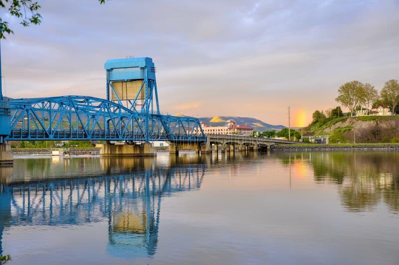 Lewiston, Clarkston błękita bridżowy odbijać w wąż rzece przeciw wieczór niebu na granicie - zdjęcie stock