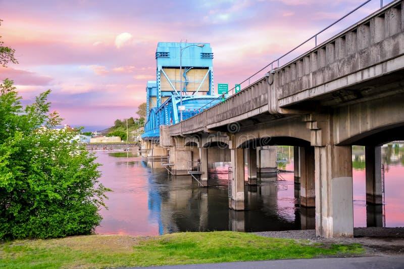 Lewiston - den Clarkston blåttbron mot himmel med rosa färger fördunklar på gränsen av Idaho och staten Washington royaltyfria bilder