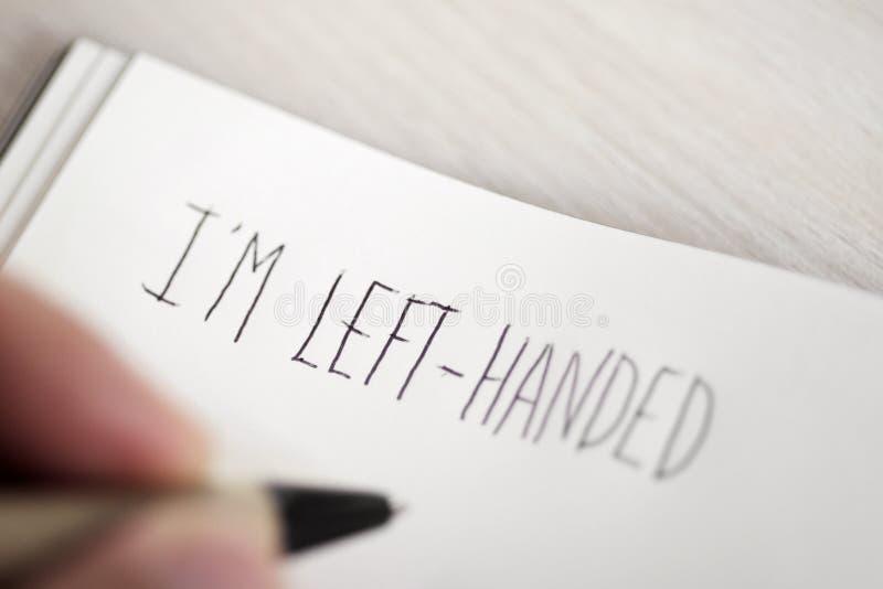 Leworęczny mężczyzna pisze tekstowi jestem leworęczni zdjęcie stock