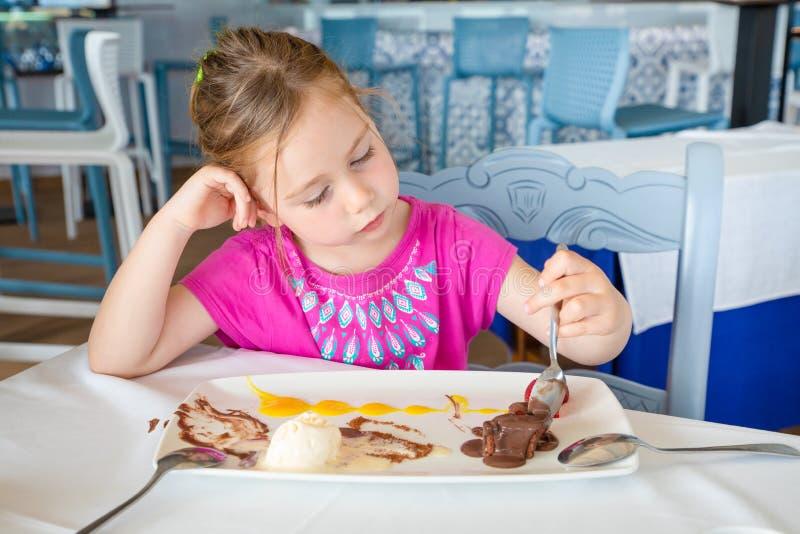 Leworęczny małej dziewczynki łasowanie czekoladowy deser w restauracji obraz stock
