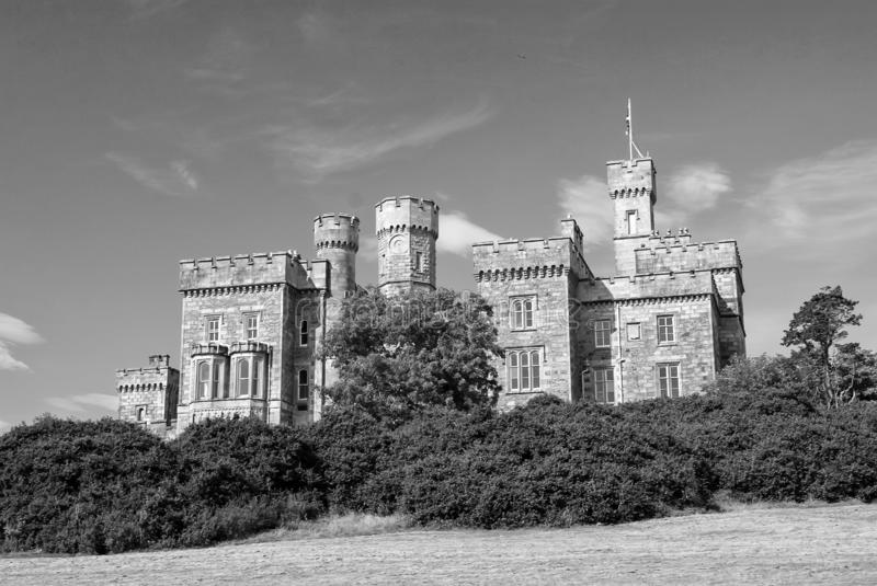 Lews Castle on blue sky in Stornoway, United Kingdom. Castle with green trees on natural landscape. Victorian style. Architecture and design. Landmark and royalty free stock image