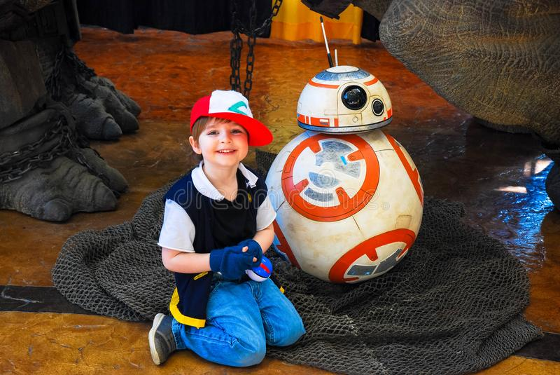 Lexington, Ky USA - mars 11, 2018 - den Lexington komiker & Toy Con Young Boy poserar med den mekaniska roboten BB8 från Star War royaltyfri bild