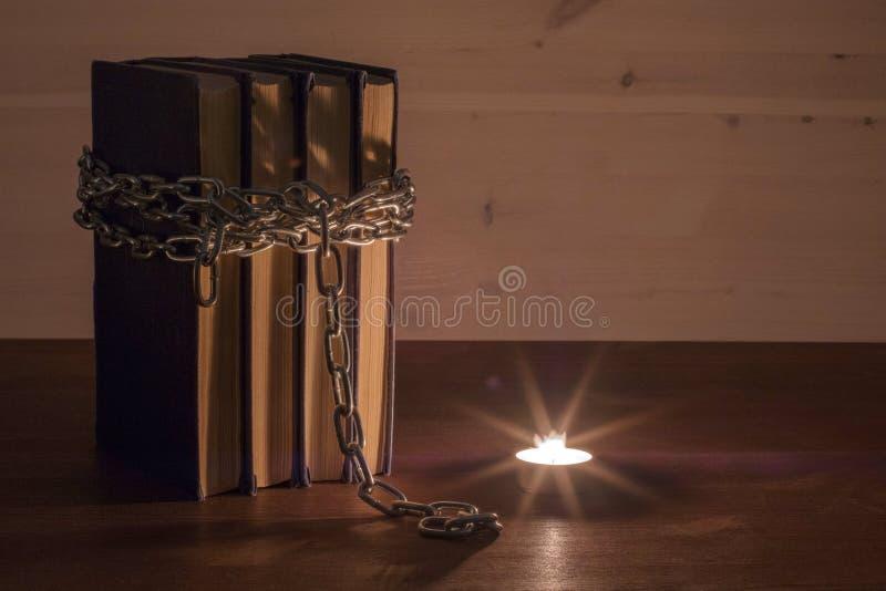 Leyendo los libros prohibidos teniendo en cuenta una vela ardiente, un libro envuelto en una cadena y una vela en la oscuridad fotos de archivo