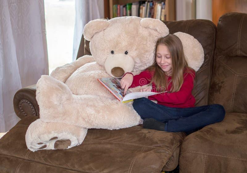 Leyendo un libro con su mejor amigo oso imagenes de archivo